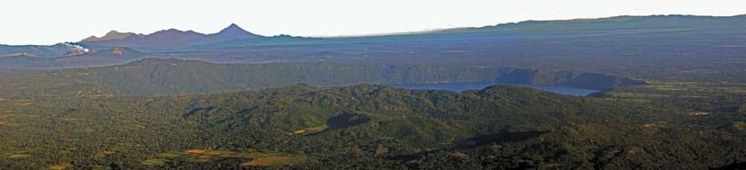 Figura 1. Vista de la Laguna de Apoyo con el humeante volcán Masaya y parte de la cordillera volcánica nicaragüense al fondo.